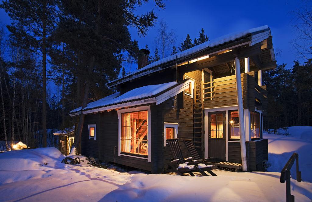 Mökki kotkala ulkopuolelta talvi-iltana